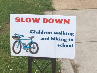sign that says slow down children walking and biking to school